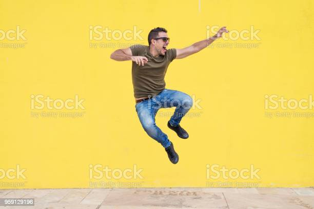 Young man with sunglasses jumping in front of a yellow wall picture id959129196?b=1&k=6&m=959129196&s=612x612&h=rxx whuez5vveubk4bwec 89lj2 jvqkogkqiwiuci4=