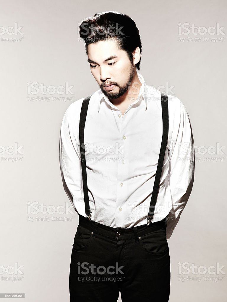 Young Man With Suspenders Looking Pensive stock photo