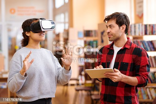 istock Young man with tablet interacting with his classmate in vr headset 1161792618