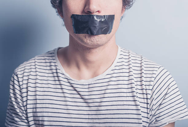 Young man with tape covering his mouth stock photo