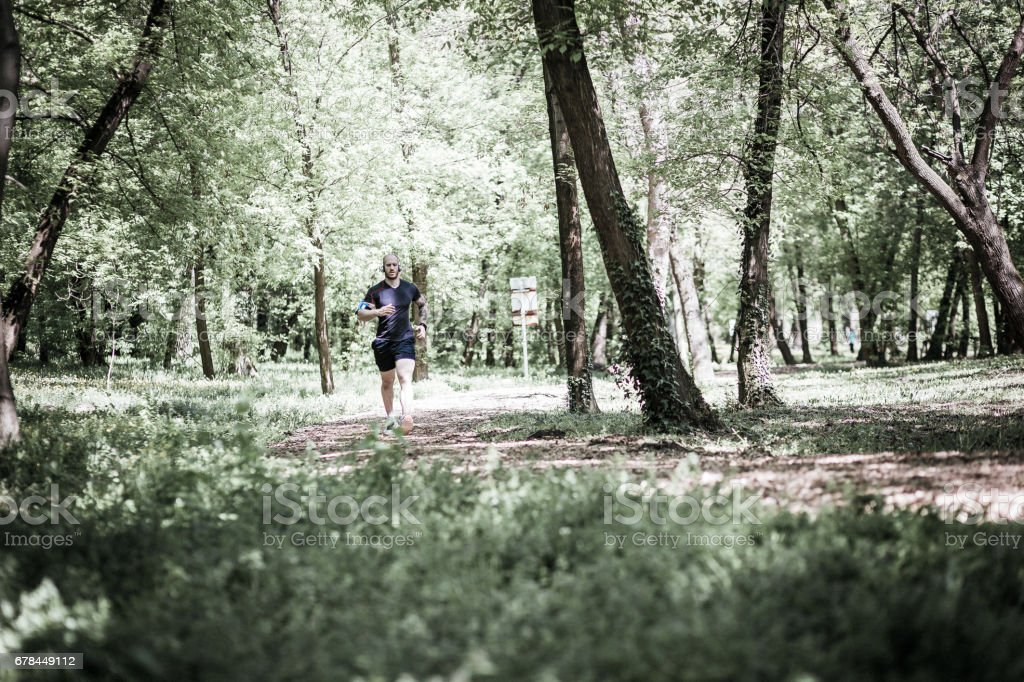 Young man with tatoo running in the park along beautiful trees. royalty-free stock photo