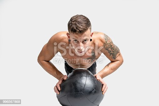 istock Young man with tattoo doing push ups. 996567868