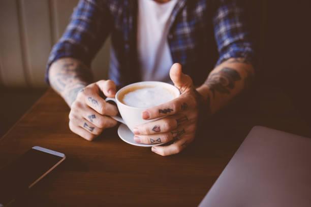 junger mann mit tattoos hält eine tasse kaffee - kaffeetasse tattoo stock-fotos und bilder
