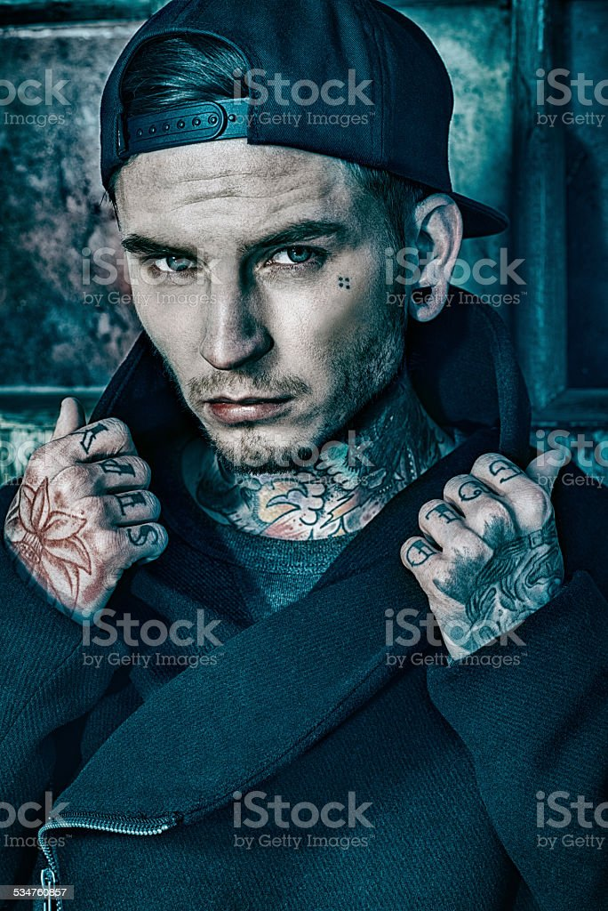 Young man with tattoos on neck and hands stock photo