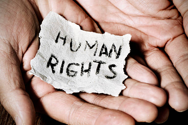 young man  with the text human rights closeup of the hands of a young man with a piece of paper with the text human rights written in it, with a dramatic effect human rights stock pictures, royalty-free photos & images
