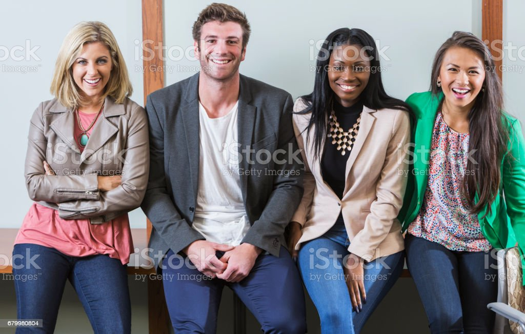 Young man with three women in smart casual attire stock photo