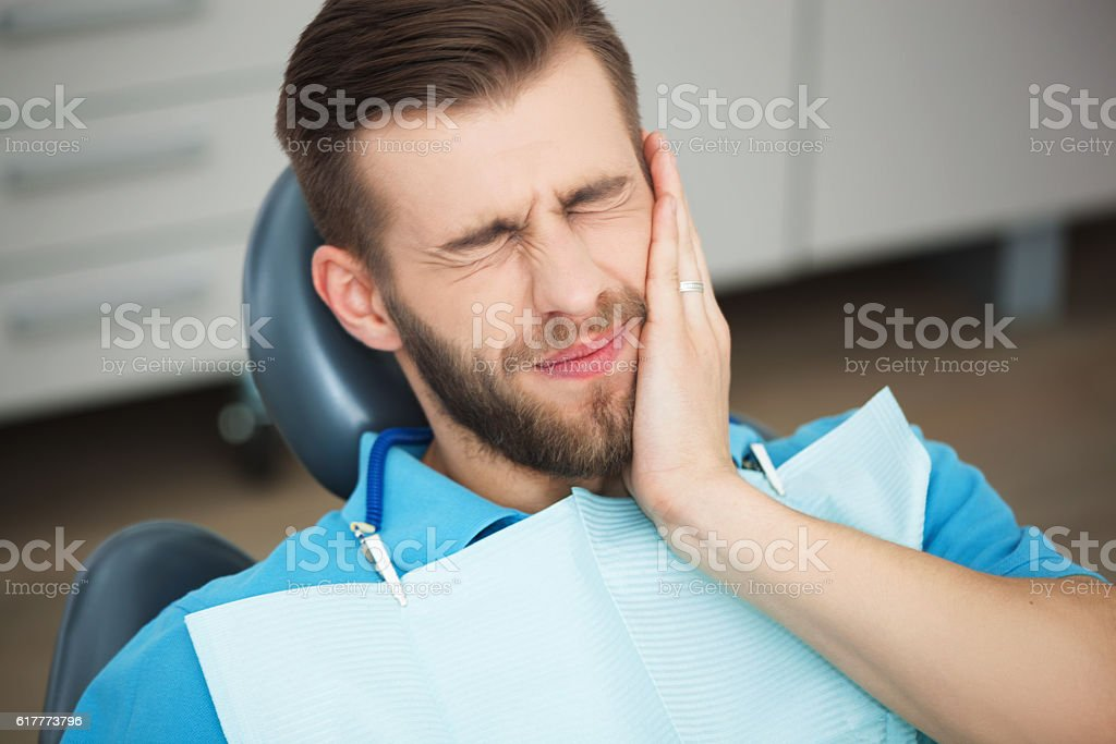 Young man with tooth pain sitting in a dentist's chair. Shot of a young man with tooth pain while sitting in a dentist's chair. Pain Stock Photo