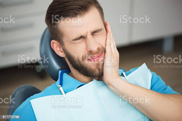 Young Man With Tooth Pain Sitting In A Dentists Chair Stock Photo - Download Image Now
