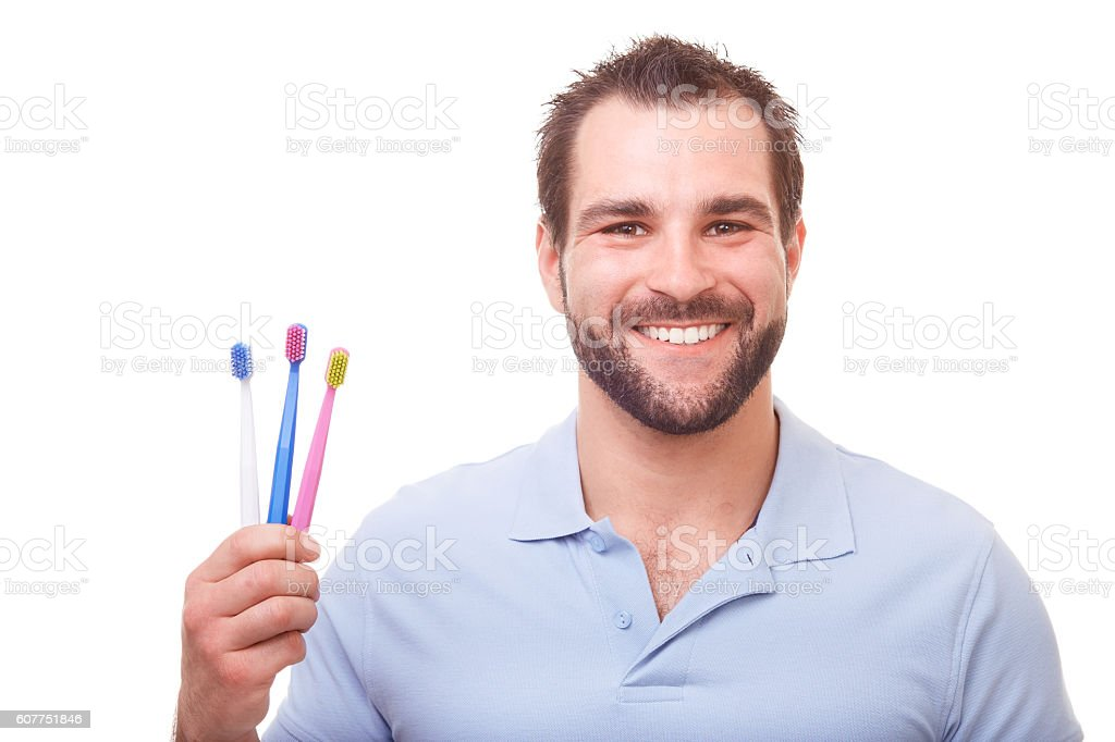 Young man with toothbrushes stock photo