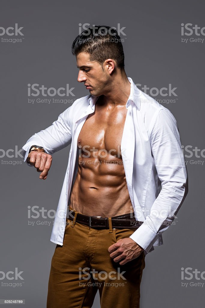 Young man with unbuttoned shirt looking at wrist watch stock photo