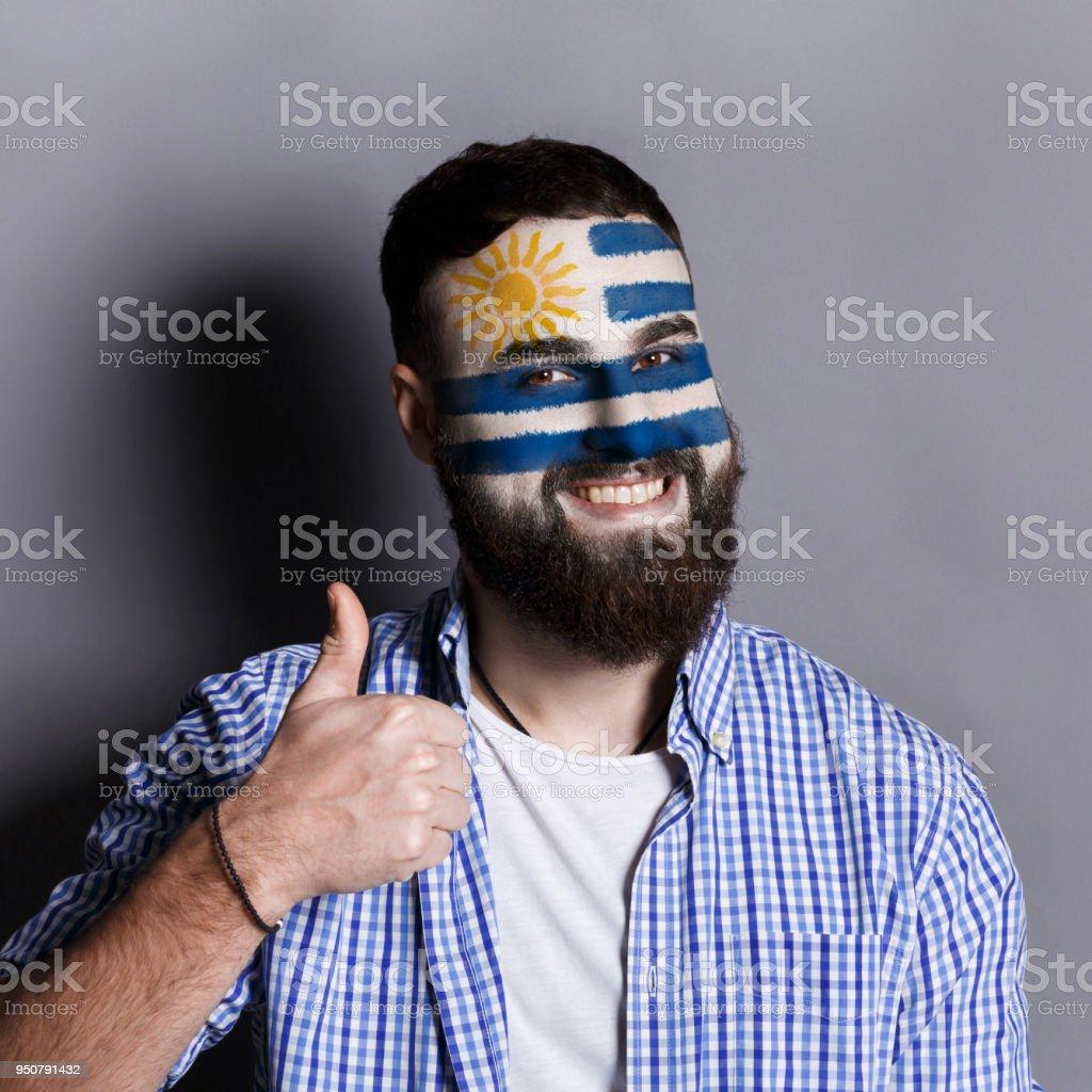 Hombre joven con la bandera de Uruguay pintada en su rostro - foto de stock