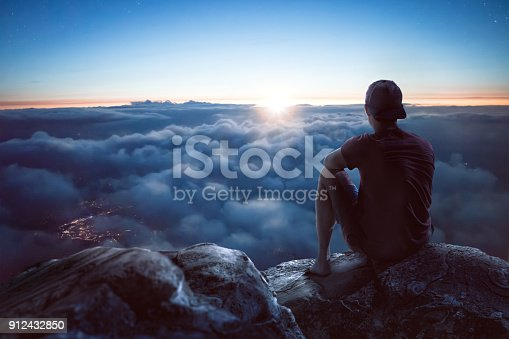 A young man is sitting on a rock on a summit overlooking a vast ocean of clouds. The sun is low and it is dark around him. Through the clouds you can see the lights of a city underneath.