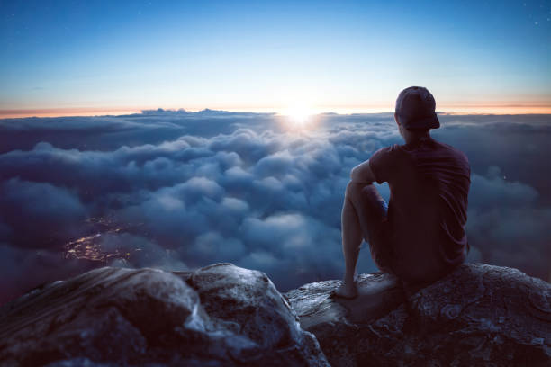 young man with view over the clouds - atmospheric mood stock photos and pictures