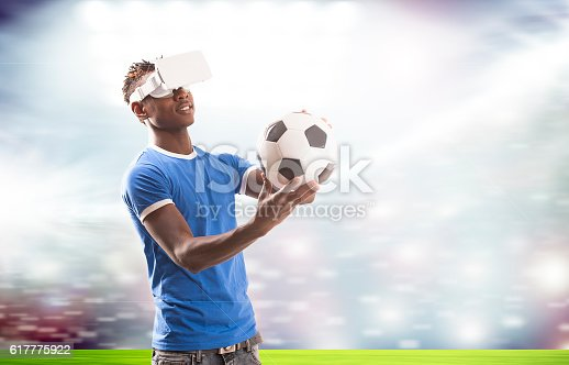 Young man with virtual reality headset or 3d glasses over football field on stadium background