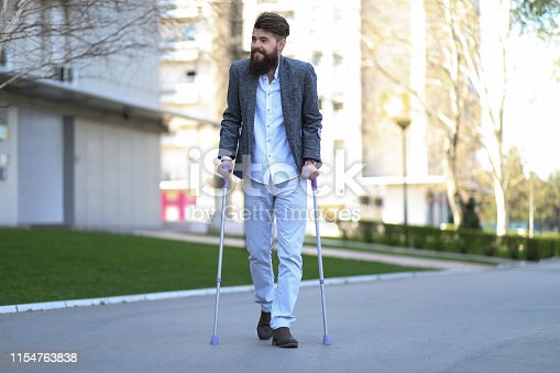 Young beautiful bearded man with walking sticks on the street, taking a stroll and enjoying sunny day. Outdoor environment