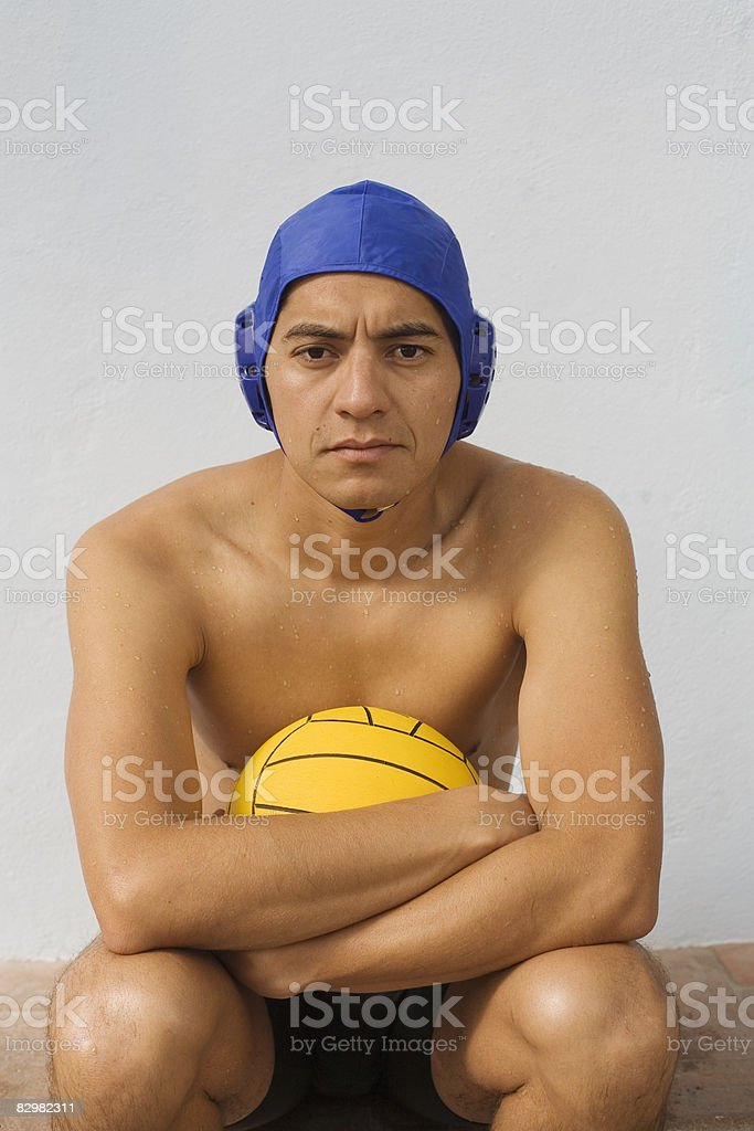 Young man with water polo ball and cap zbiór zdjęć royalty-free