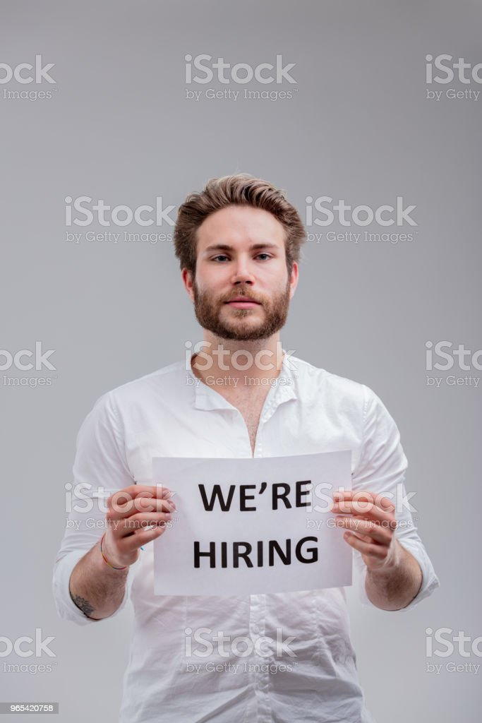 Young man with We are hiring sign zbiór zdjęć royalty-free