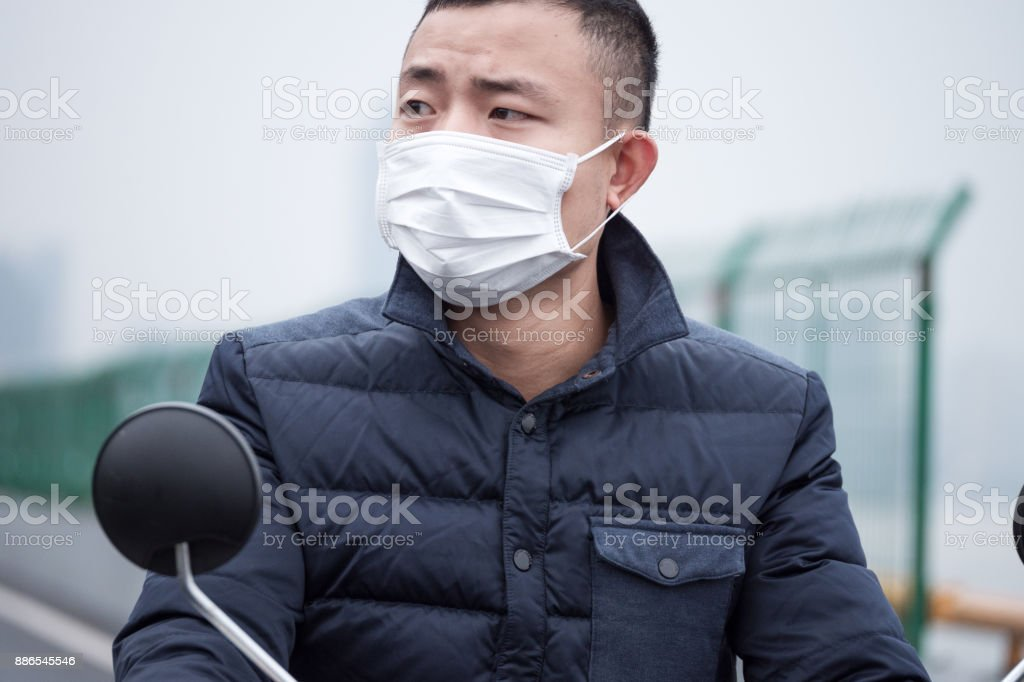 young man with white mask rides on motorcycle stock photo