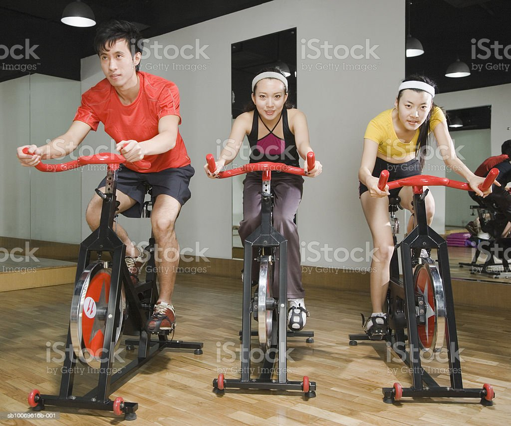 Young man with women on exercise bike in gym foto de stock libre de derechos