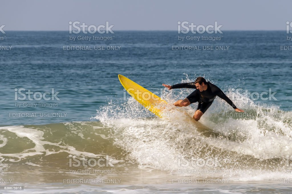 Young man with yellow surf board surfing in Zuma Beach, California stock photo