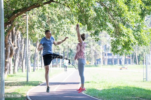 Young man athlete without leg with prosthesis exercise stretches with female trainer in green park in nature on trim track.