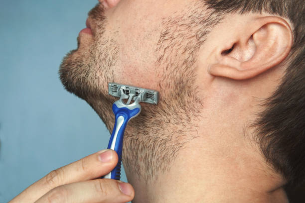Young man without shaving cream on his face, grooming his beard with straight razor, stock photo