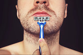 istock Young man without shaving cream on his face, grooming his beard with straight razor, on black background 969969760