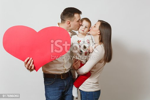 istock Young man, woman holding, kissing, hugging little cute child boy with big red heart isolated on white background. Father, mother, little kid son. Parenthood, family, parents and children concept. 917686050