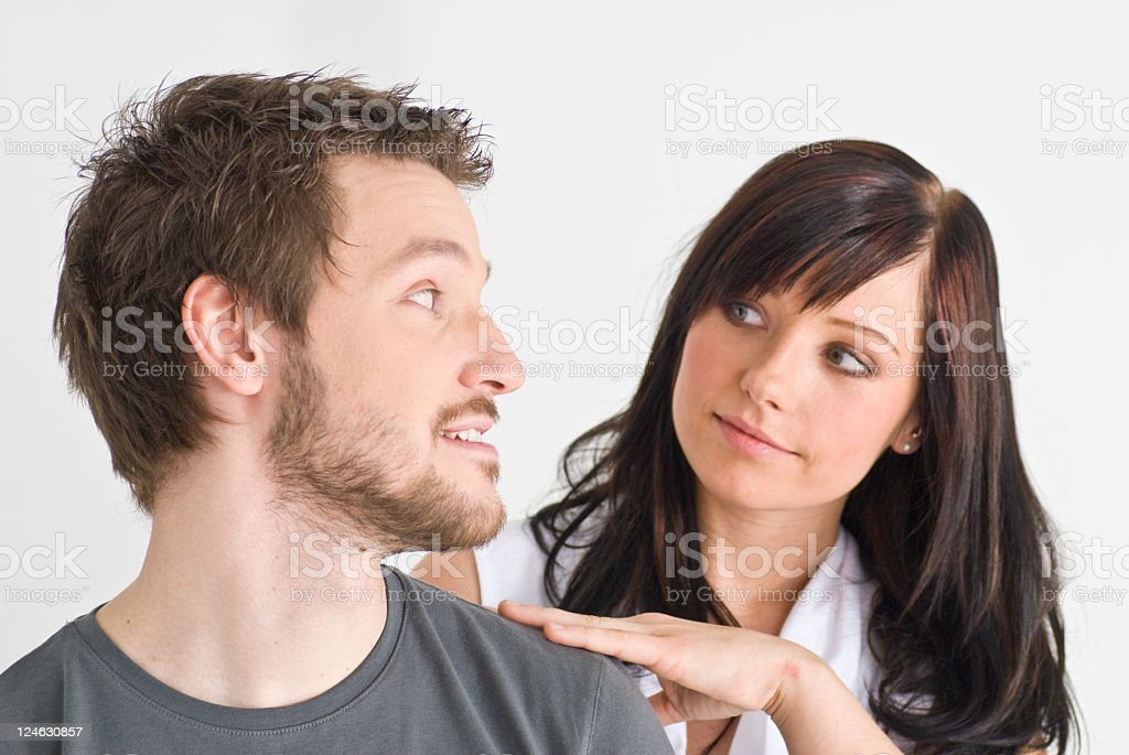 Young man & woman looking to each other over man's shoulder royalty-free stock photo