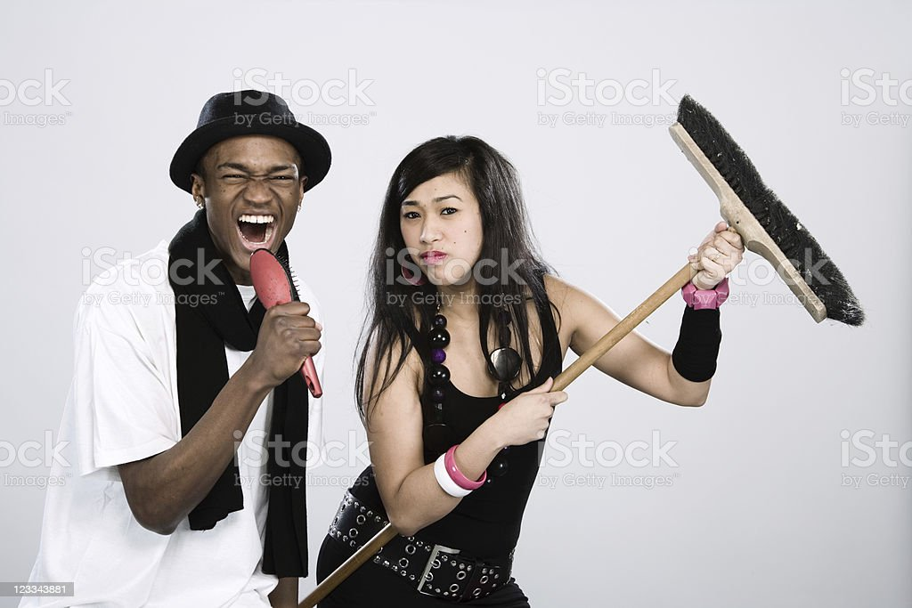 Young man & woman using household items as fake instruments stock photo