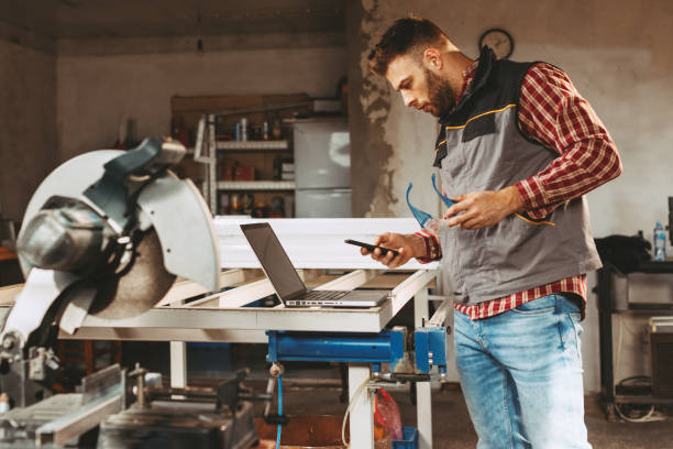 Young man work in home workshop using smartphone stock photo