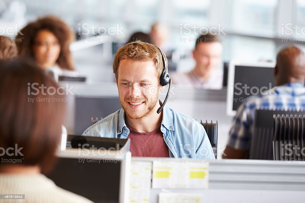 Young man working at a computer in a call centre stock photo