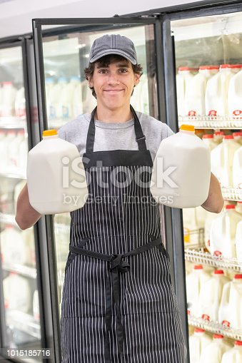 Smiling Young man working at a supermarket holding two gallons of milk