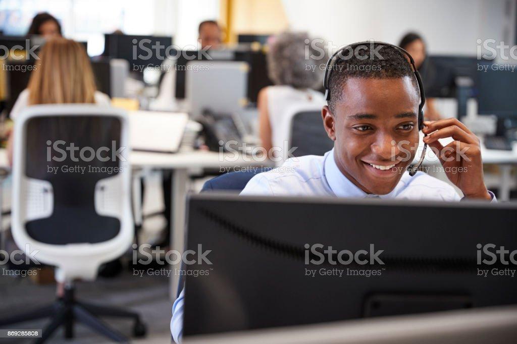 忙しいオフィスでヘッドセットとコンピューターで働いていた若い男性 ストックフォト