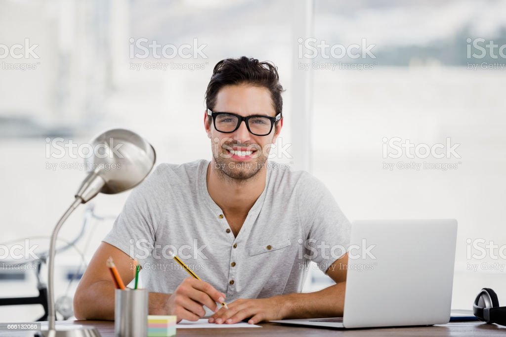Young man working at his desk stock photo