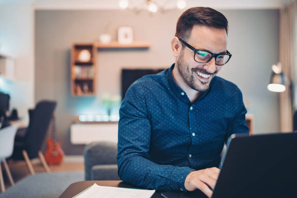 Young man working at home in the evening Businessman using laptop at home using computer stock pictures, royalty-free photos & images
