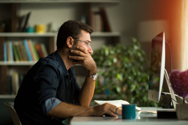 Young man working at home in the evening stock photo