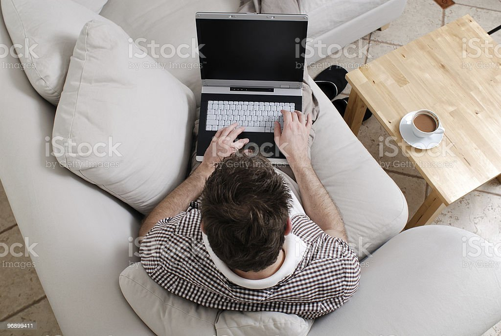 Young man working at home on a laptop royalty-free stock photo