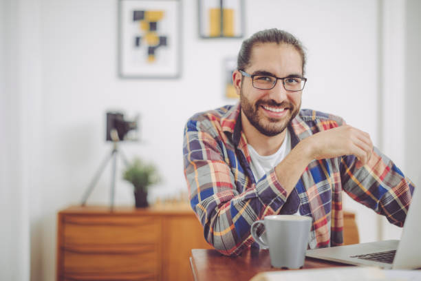Young man working at home Young man working at home man bun stock pictures, royalty-free photos & images
