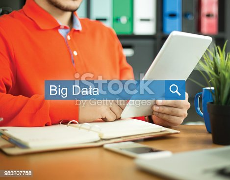 917307226istockphoto Young man working in an office with tablet pc and searching BIG DATA word on internet 983207758