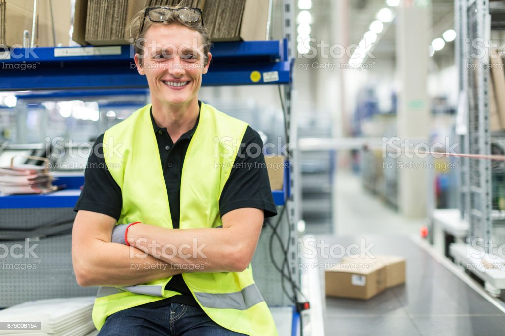Young man working in large distribution warehouse stock photo