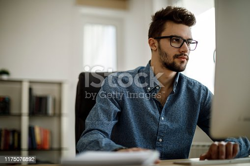 872006502 istock photo Young man working in the office 1175076892