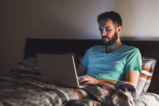Young man working late in bed on a laptop stock photo