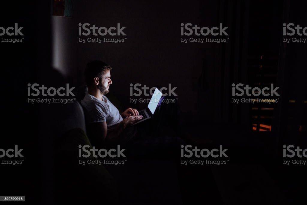 Junger Mann spät im Bett auf einem Laptop arbeiten – Foto