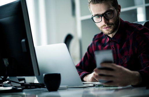 Portrait of young man working late and using smartphone in his office