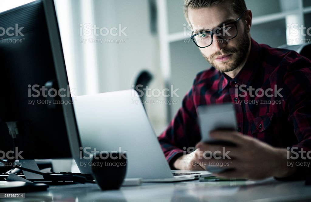 Young man working late in his office stock photo