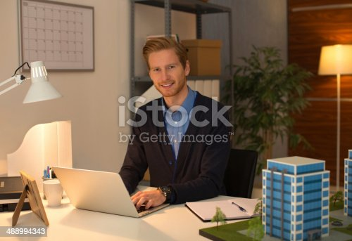 istock Young man working late. 468994343
