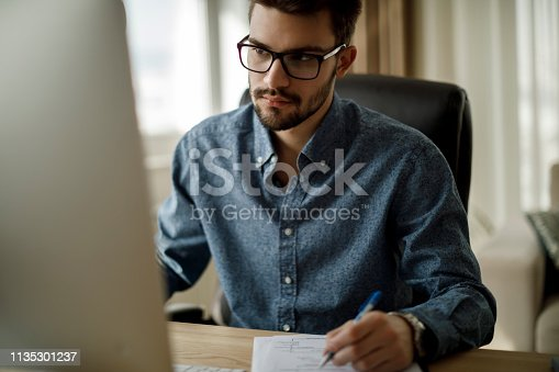 Young man working on computer and taking notes