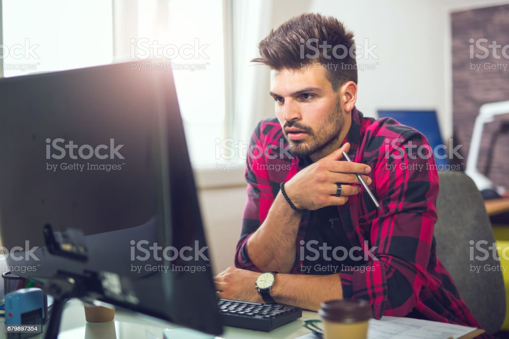 Young man working on computer in modern office Handsome Caucasian man at work desk facing flat screen computer 20-24 Years Stock Photo