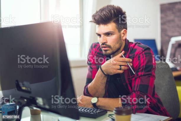 Young Man Working On Computer In Modern Office Stock Photo - Download Image Now